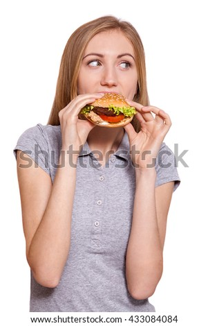 Food on the go.Closeup of a young caucasian woman eating a big hamburger, isolated on white background. - stock photo