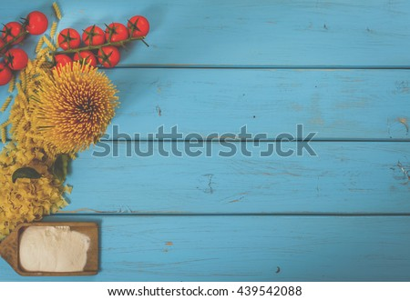 Food or cooking background with pasta, tomato, spaghetti, penne, basil and flour on blue wood table. Top view. Copy space. - stock photo