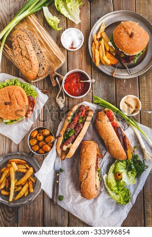 Food party table concept. Grill Sausage Sandwiches with two hamburger , potatoes fried and various sauce served on rustic table from above.  - stock photo