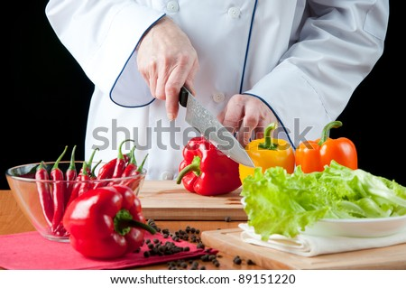 Food preparation – chef cutting bell peppers, over a black background - stock photo