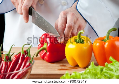 Food preparation: chef cutting bell peppers, studio shot - stock photo