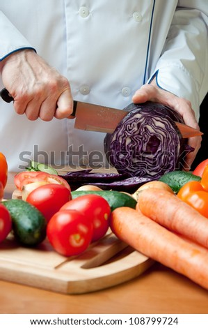 Food preparation � cutting a fresh red cabbage - stock photo