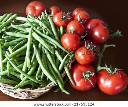 Food preparation on the kitchen table, green beans and ripe cherry tomatoes - stock photo