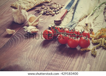 Food. Proper nutrition. Fish, fresh vegetables, cereals, pasta, greens, corn bread. - stock photo