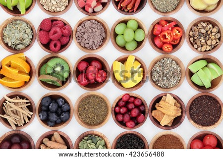 Food selection for cold and flu remedy to boost immune system, high in vitamins, anthocyanins, antioxidants and minerals in wooden bowls over white background. - stock photo