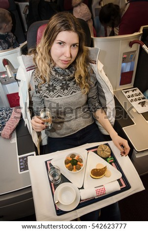 Food served for woman passenger on board of airplane on the table. Fresh meal with desert and glass of wine. Italian tasty cuisine.
