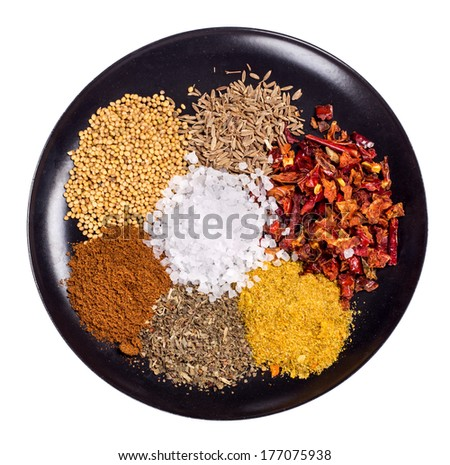 food spices on black plate Isolated on white background - stock photo
