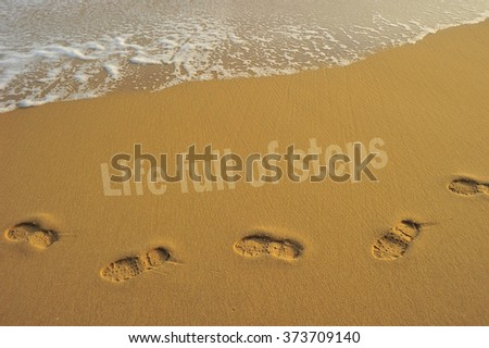 """Food steps on the beach with the effect of morning sun light on the sand and the wave with the word """"life full of steps """" . slightly soft due to long exposure. - stock photo"""
