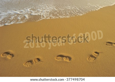 "Food steps on the beach with the effect of morning sun light on the sand and the wave with the word "" 2016 years of good"" . slightly soft due to long exposure. - stock photo"