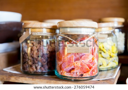 food, storage and eating concept - close up of jars with dried fruits at grocery - stock photo