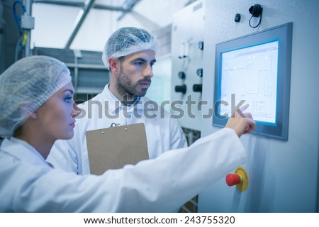 Food technicians working together in a food processing plant - stock photo