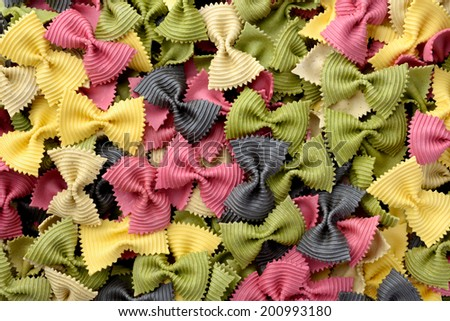 Food: uncooked multicolor farfalle pasta background - stock photo