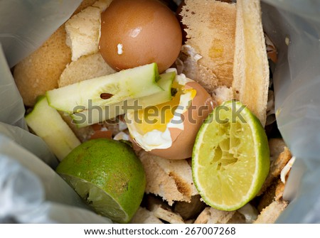 Food waste inside a plastic biodegradable bag. The bag contains limes, green limes, eggs, and toast. This bag is collected and the contents converted to compost.  - stock photo