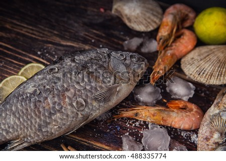 Food wooden background with frozen Seafood, sticks, lime, salt, cubes of ice