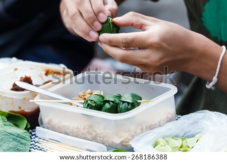 Food wrapped in leaves or Miang Kham with hand of seller background at local market, Thailand - stock photo