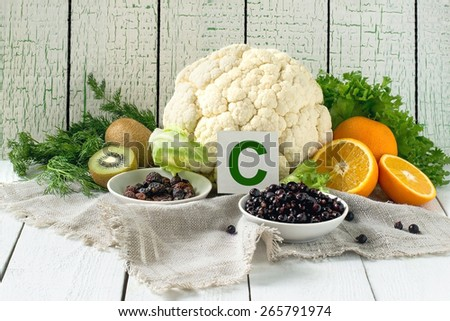 Foods containing vitamin C (cauliflower, lettuce, dill, dried rose hips, currants, oranges, kiwi) on a linen napkin - stock photo