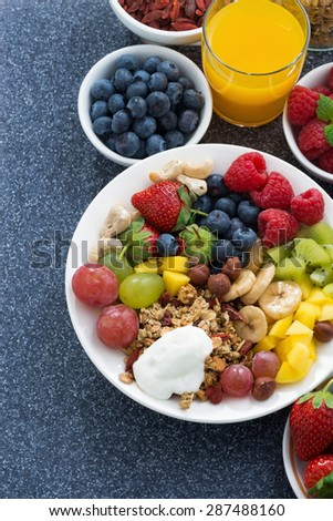 foods for a healthy breakfast - fresh berries, fruits, nuts and muesli on dark background, vertical, top view - stock photo