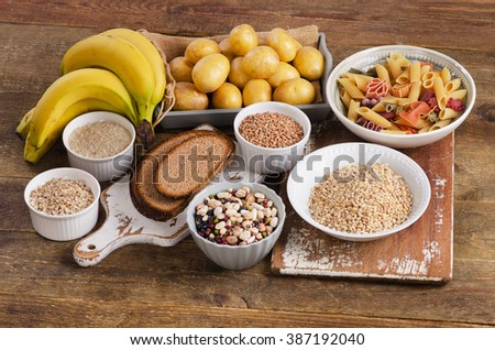 Foods high in carbohydrate on wooden background. Top view - stock photo