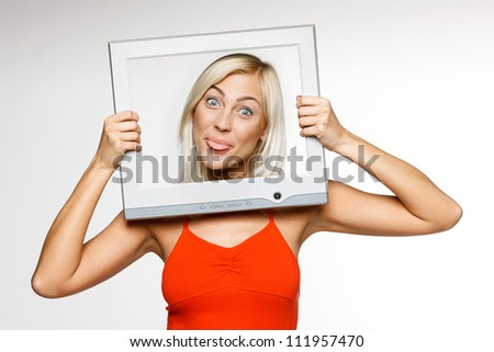 Fooling young blond female looking through the TV / computer screen frame, sticking out her tongue - stock photo