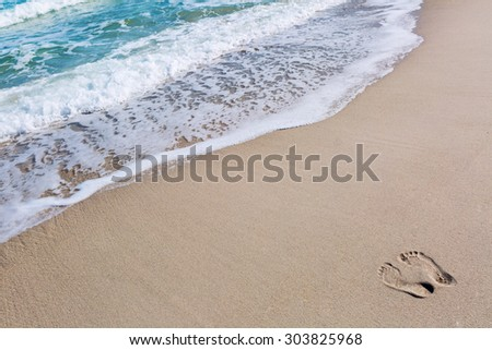 Foor prints in sand at beach - stock photo
