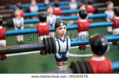Foosball player in a white and blue uniform made of metal.