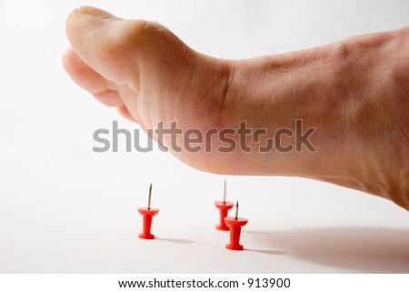 Foot and tacks - illustrating foot pain - stock photo
