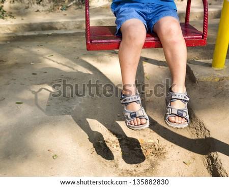 Foot baby swinging on swing at playground - stock photo