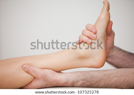 Foot being held by a doctor indoors - stock photo