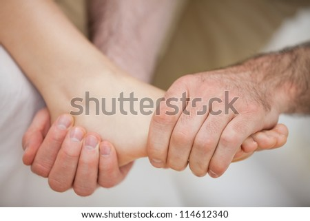 Foot being held by a practitioner indoors - stock photo