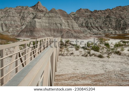 Foot Bridge:  A hiking trail crosses a narrow bridge over a flash flood area in the Badlands of South Dakota.  - stock photo