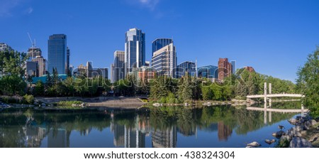 Foot bridge reflected in the Bow River at princes island park and the urban skyline in Calgary Alberta.