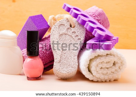 Foot care and cosmetics. Pedicure accessories set tools : pumice with footprint, towel, toe separators and pink varnish - stock photo