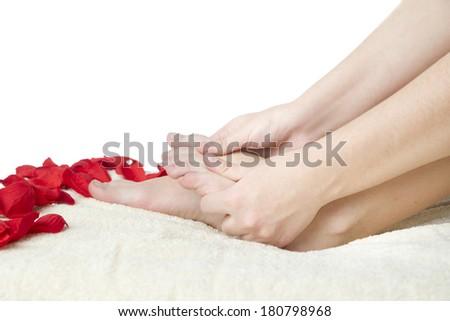 Foot care. Beautiful female legs and rose petals - stock photo