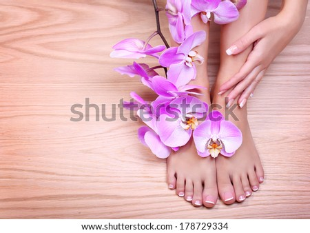 Foot care. Pedicure with pink orchid flowers on wooden background. Beautiful female feet and hand with french manicure. Spa - stock photo
