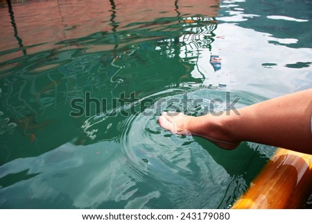 Foot dipping into the fresh water in lake among daytime natural light represent the relaxation activity. - stock photo