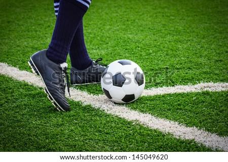 foot kicking soccer ball on corner - stock photo