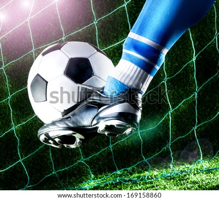 Foot kicking soccer ball on playing field with dark background - stock photo