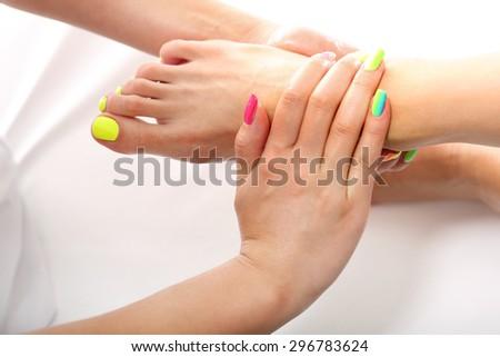 Foot massage. Beautician massaging woman's foot, acupressure treatment - stock photo