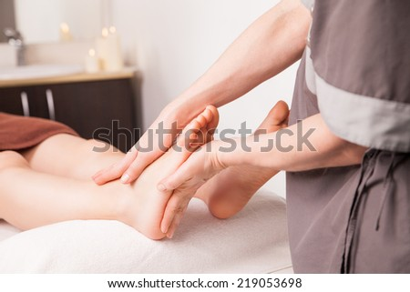 Foot massage for a woman in a luxury spa - stock photo