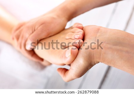 Foot massage in the spa salon.Woman in a beauty salon for pedicure and foot massage. - stock photo
