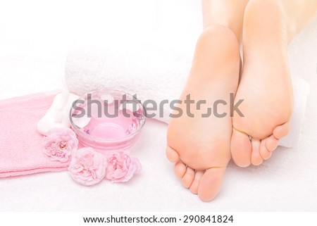 Foot massage in the spa with pink rose