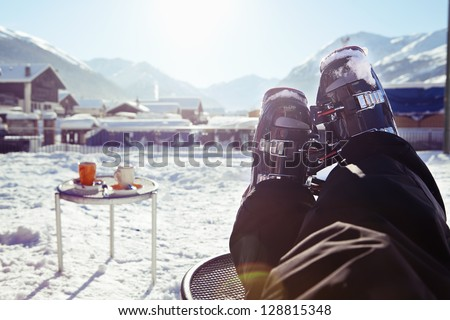 Foot of a skier wearing ski boots, sitting and having rest in a cafe at the sun in front of winter mountains and village panorama - stock photo