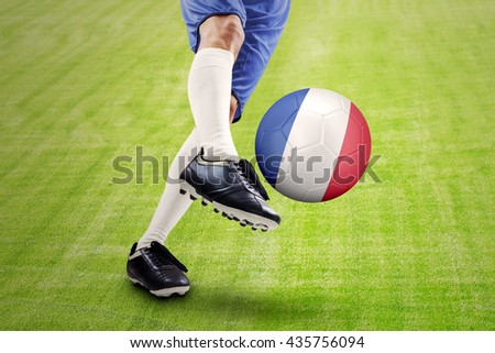 Foot of a soccer player kicking a ball with a France flag at field. Concept of european football championship 2016 - stock photo