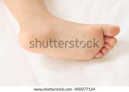 Foot of asian baby on white bedcovers.