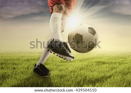 Foot of football player kicking a soccer ball on the green field, shot with sunlight in the morning - stock photo