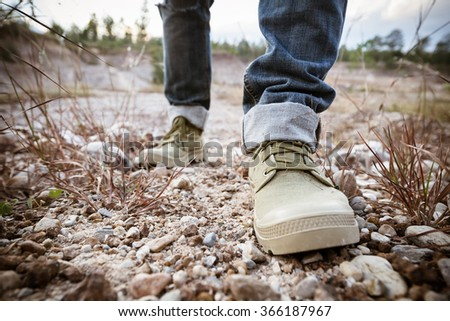 Foot of man walking on ground rock