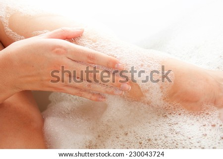 Foot of the woman in bathing covered with foam