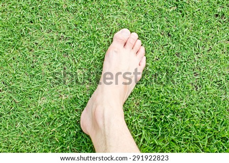 Foot on grasses background