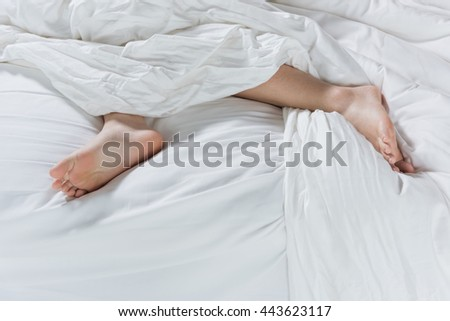 foot on white cotton bed background