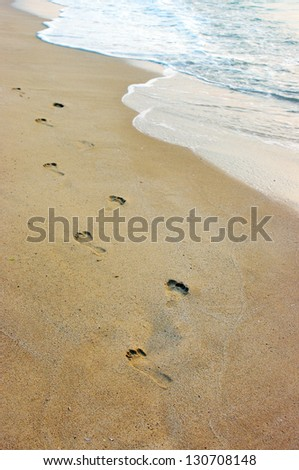 Foot prints on a sandy beach - stock photo